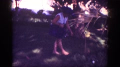 1962: family garden lady plucking flowers walking holding puppy wearing hat Stock Footage