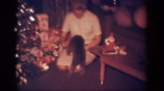 1962: a woman is holding her dog under the christmas tree BLAINSPORT Stock Footage