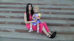 Mother and daughter in festive dresses play on the stairs. Stock Footage