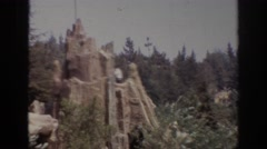 1962: sweeping views of a mountain scene with large trees and people moving Stock Footage