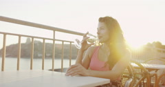 4K Portrait of beautiful woman drinking wine outdoors as the sun begins to set Stock Footage