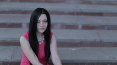 Beautiful brunette girl sits in a pink evening dress on a stone staircase. Stock Footage