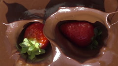 Strawberries falling splashing into chocolate slow motion Stock Footage