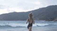 Pretty woman in black swimsuit at the beach Stock Footage