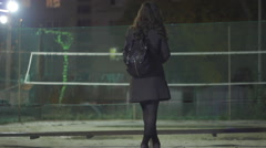 Gothic girl is drinking tea near the empty playground at night in the city Stock Footage