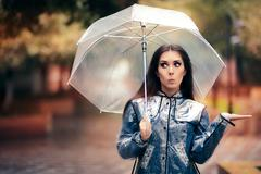 Woman with Transparent Raincoat and Umbrella Checking for Rain Stock Photos