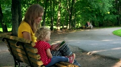Woman with little girl using tablet computer sit on bench in park Stock Footage