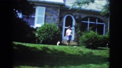 1962: lady coming out house walking towards garden trees round greenery puppy Stock Footage