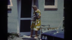 1962: elderly woman holding dog and moving lawn chair. RALEIGH NORTH CAROLINA Stock Footage