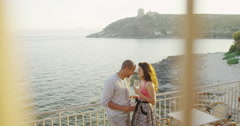 4K Happy couple drinking wine at outdoor bar or restaurant beside the sea Stock Footage