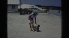 1962: woman training her poodle to obey and sit while they are at the beach Stock Footage