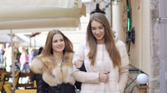 Two glamour girls walking in furry coats in shopping center. Slowly Stock Footage