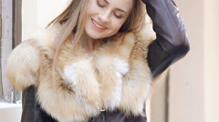 Cute girl posing in furry jacket on the street. Slow motion Stock Footage