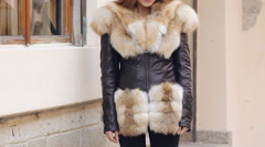 Young cute girl posing in furry jacket on the street. Slow motion Stock Footage