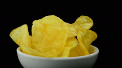 Potato chips in a bowl rotating on black background Stock Footage