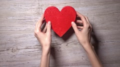 Girl placing four red hearts on a wooden table, top view. Flower, care, love Stock Footage