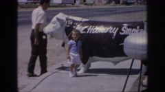 1967: man and young boy standing by a statue of a cow OKLAHOMA Stock Footage