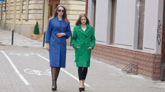 Two women walks runway in cashmere coats on the street. Slowly Stock Footage