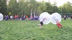 Falling boys in the difficult game zorb Stock Footage