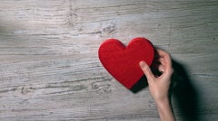 Girl placing two red hearts on a wooden table, top view. Romance, love Stock Footage