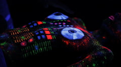 The artist draws a fluorescent powder on the body of a naked girl DJ mixer Stock Footage