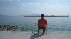 The man in the red shirt sitting on the chair and enjoys stunning views of the Stock Footage