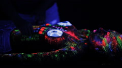 Topless girl painted in UV powder as a DJ panel Stock Footage