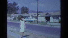 1966: woman walking down sidewalk in white dress SACRAMENTO CALIFORNIA Stock Footage