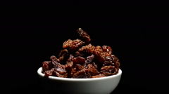Raisins or dried grape in a bowl rotating on black background Stock Footage