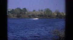 1966: blue lake with speedboat crossing and other boat pulling skier and shore Stock Footage