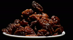 Raisins or dried grape in a bowl gyrating on black background Stock Footage