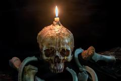 Skull with candle light on top and bone on grunge wood on black background us Stock Photos