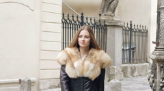 Cute girl posing in furry jacket and smiling on the street. Slowly Stock Footage