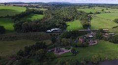 Aerial shot of a steam train passing rural houses. Stock Footage