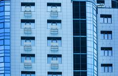 Windows of multi-storey building glass and steel office lighting Stock Photos