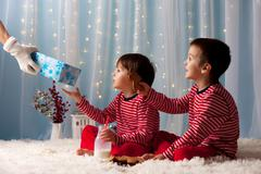 Two little boys in pajamas, waiting from Santa Claus, Santa bringing them pre Stock Photos