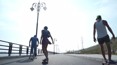 Two guys with the girl riding on the promenade in long boards Stock Footage