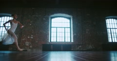 Beautiful girl dancer performs a jump, and classical ballet in the loft design Stock Footage