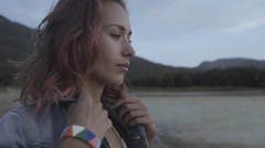 Sensual model with pink curly hair in denim jacket posing outdoors Stock Footage