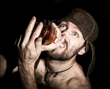 Dark portrait of scary evil sinister bearded man with smirk, holding a bottle of Stock Photos