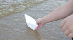 Girl Launches the a Paper Boat in the Sea Stock Footage