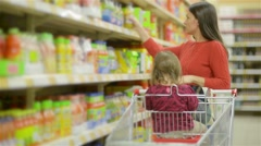 Mother and child walks along wholesale shelves and taking goods in shop trolley Stock Footage