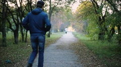 Senior man walking and relaxing in autumn park.  Stock Footage