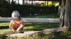 Cute little girl collects sticks of trees from the grass to make a bouqet Stock Footage