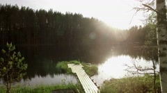 Moving over a wooden dock over water at a sunny forest lake, drone shot Stock Footage