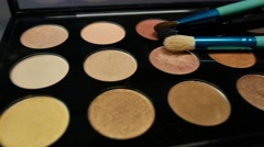 Three brushes lying on a make-up palette, the shot is moving from right to left Stock Footage