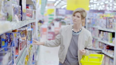 Young woman choosing toy car for boy in supermarket Stock Footage