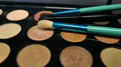Three brushes lying on a make-up palette, the shot is moving Stock Footage