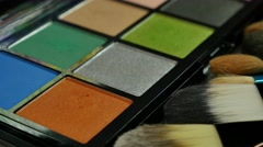 A make-up artist using and applying an orange eye shadow color from a palette Stock Footage