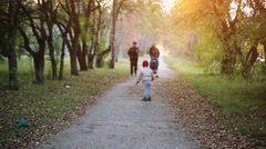 Happy family walking in autumn park at sunny day. 1920x1080 Stock Footage